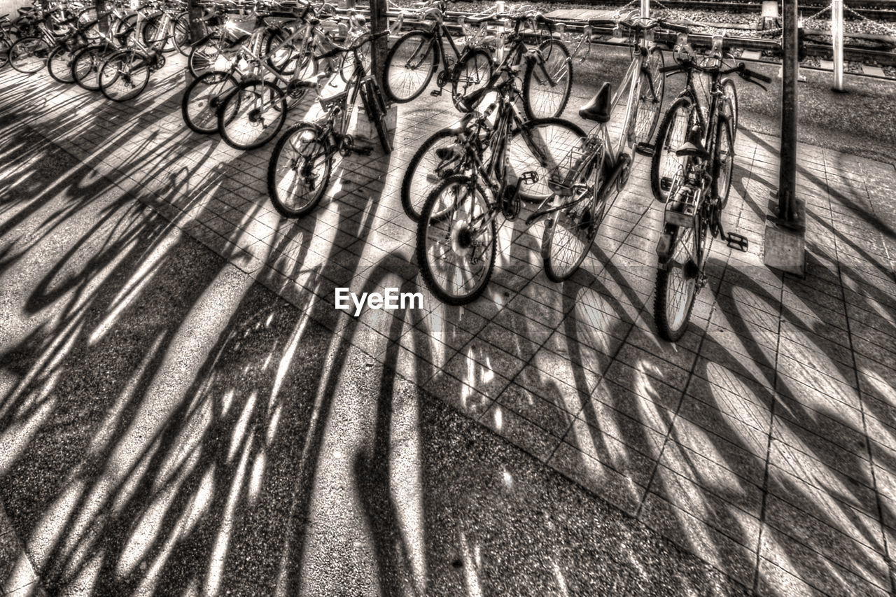 bicycle, high angle view, outdoors, day, metal, no people, shadow, sunlight, bicycle rack, nature, close-up