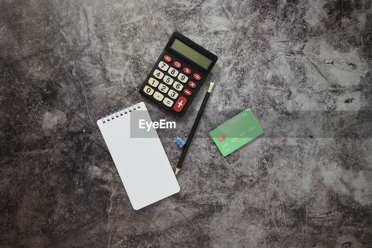 high angle view, paper, no people, indoors, directly above, table, calculator, still life, communication, technology, finance, close-up, document, retro styled, connection, business, number, blank, concrete