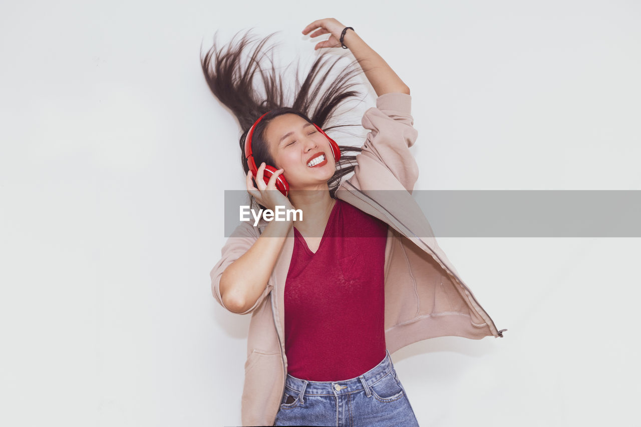 YOUNG WOMAN STANDING AGAINST WHITE WALL