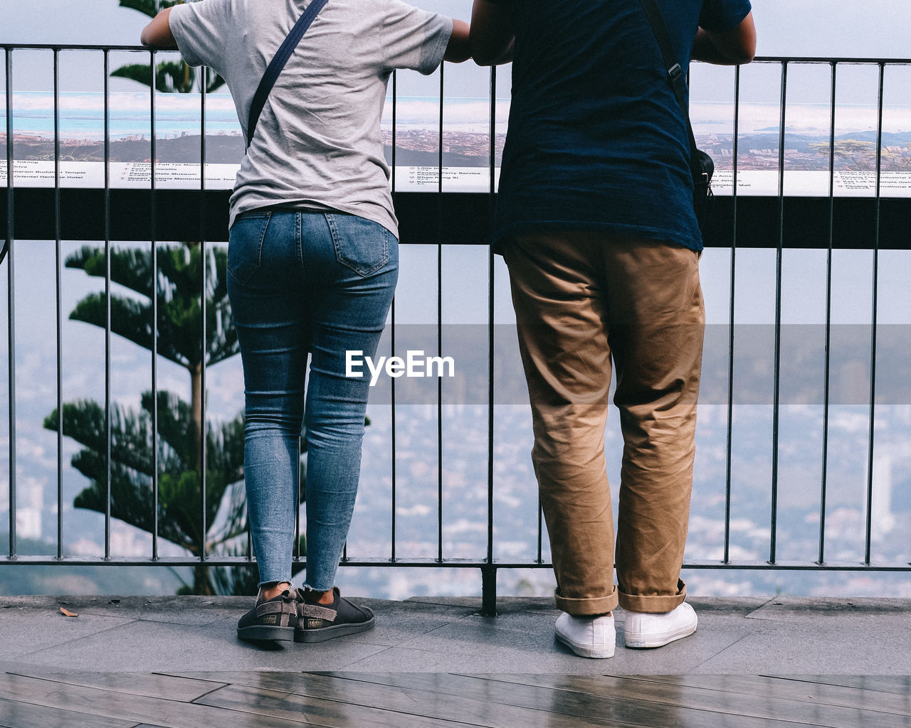 Low section of couple standing against railing