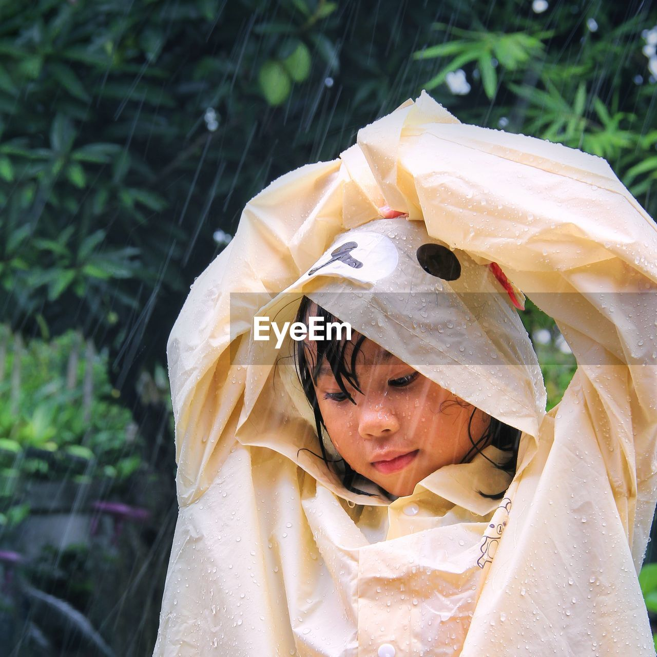 Close-up portrait of a beautiful young woman in rain