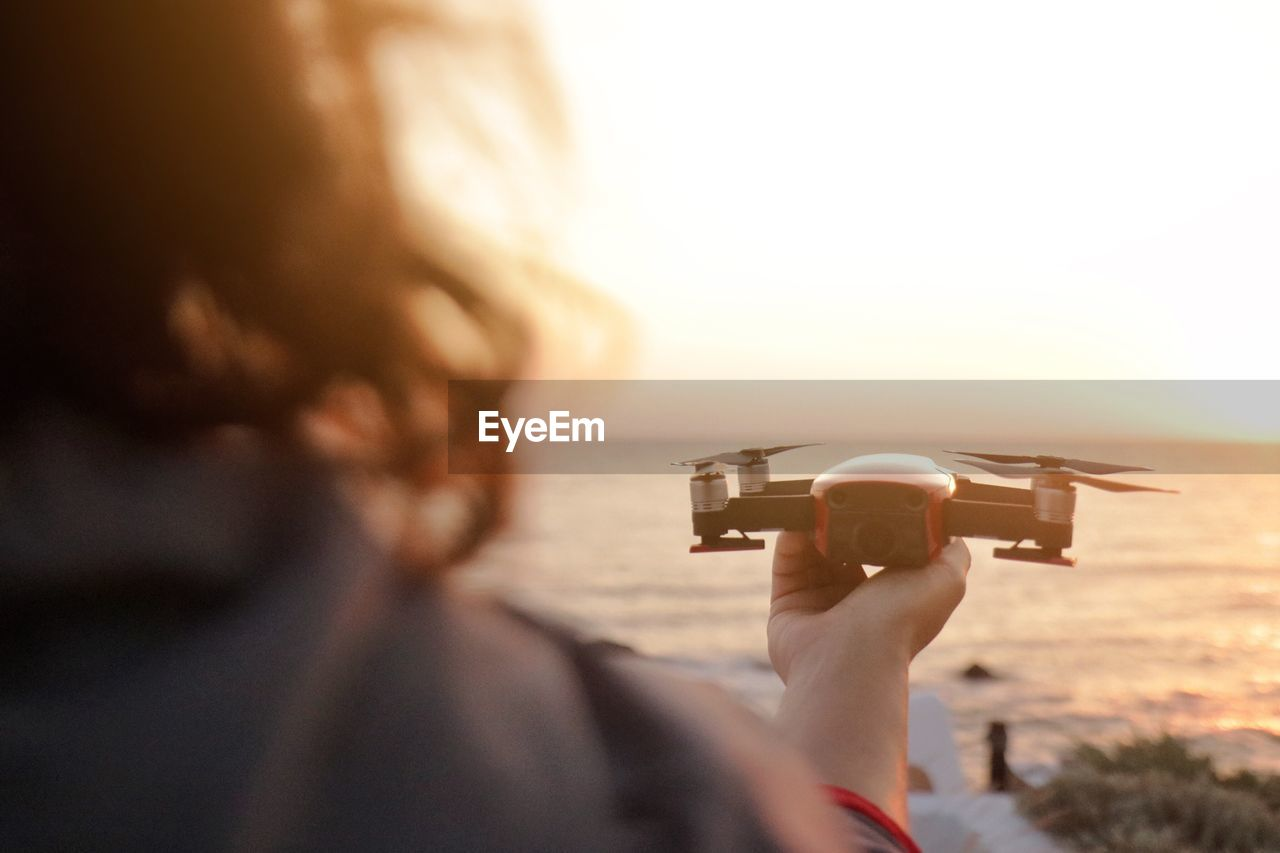 Rear View Of Woman Holding Drone At Beach During Sunset