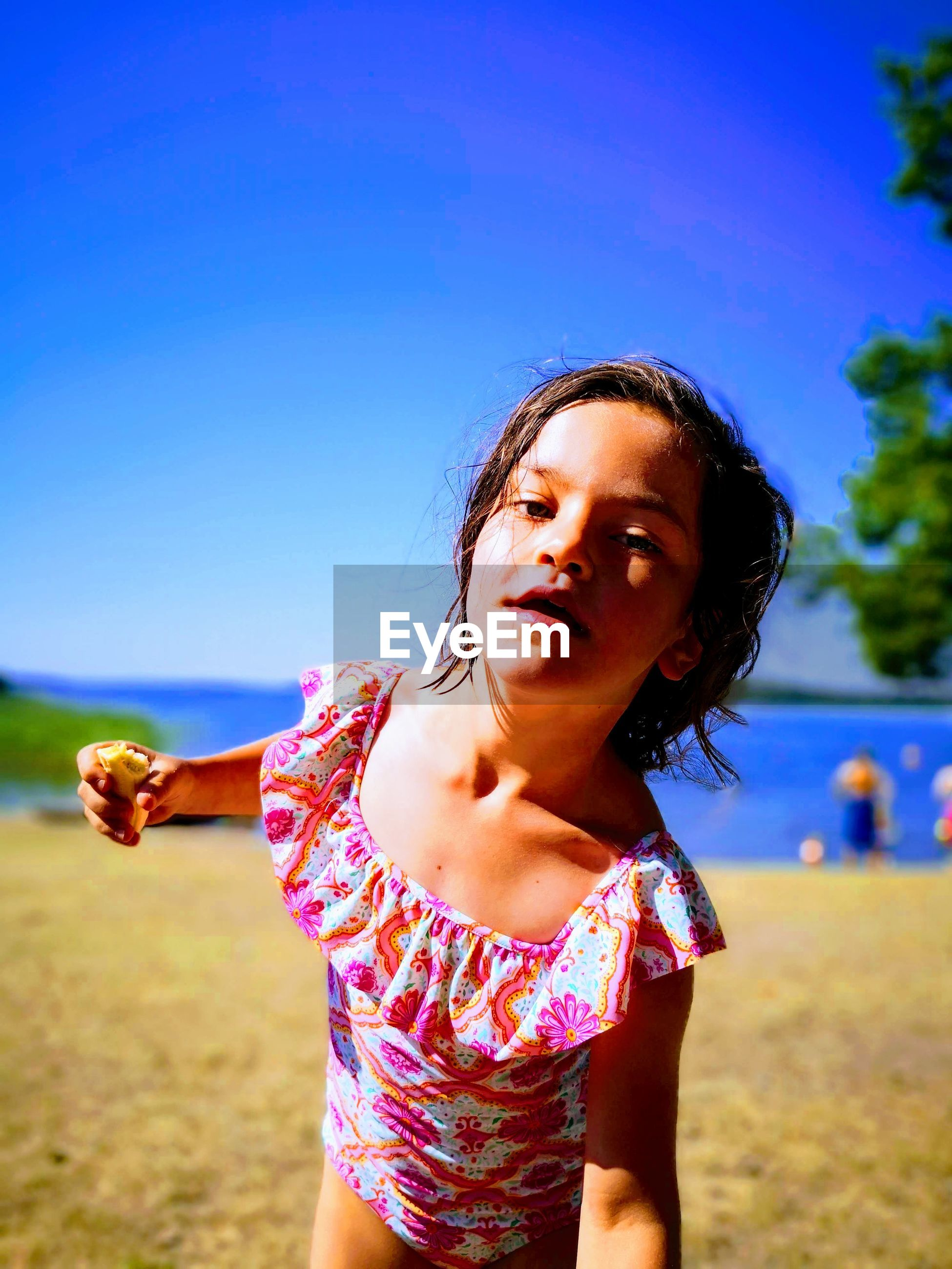 Portrait of cute girl standing at beach against clear blue sky
