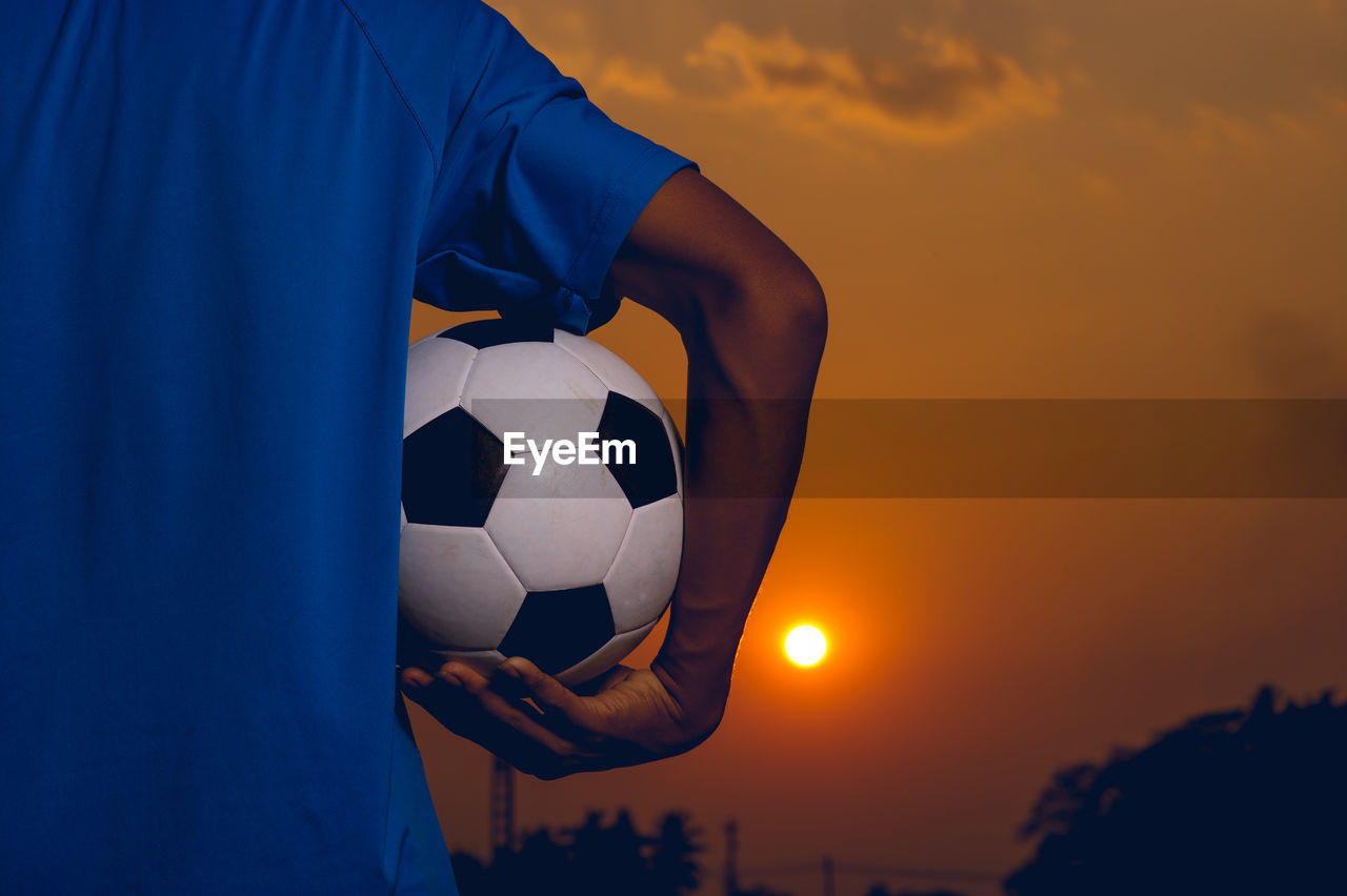 sunset, sky, soccer, ball, sports equipment, sport, soccer ball, team sport, one person, orange color, midsection, real people, holding, leisure activity, lifestyles, nature, blue, men, cloud - sky