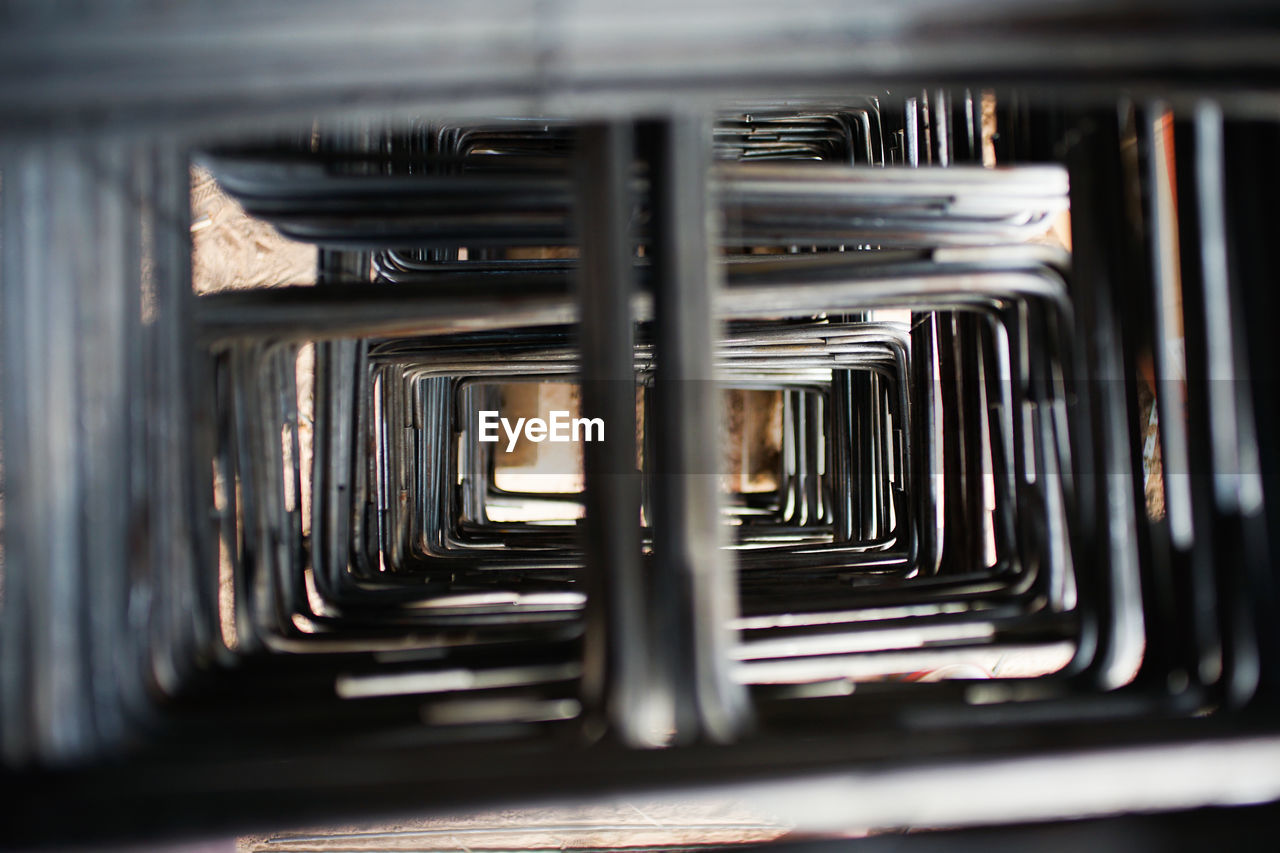 selective focus, metal, no people, indoors, in a row, close-up, large group of objects, still life, rail transportation, pattern, focus on background, stack, transportation, abundance, public transportation, silver colored, reflection, repetition, arrangement, empty