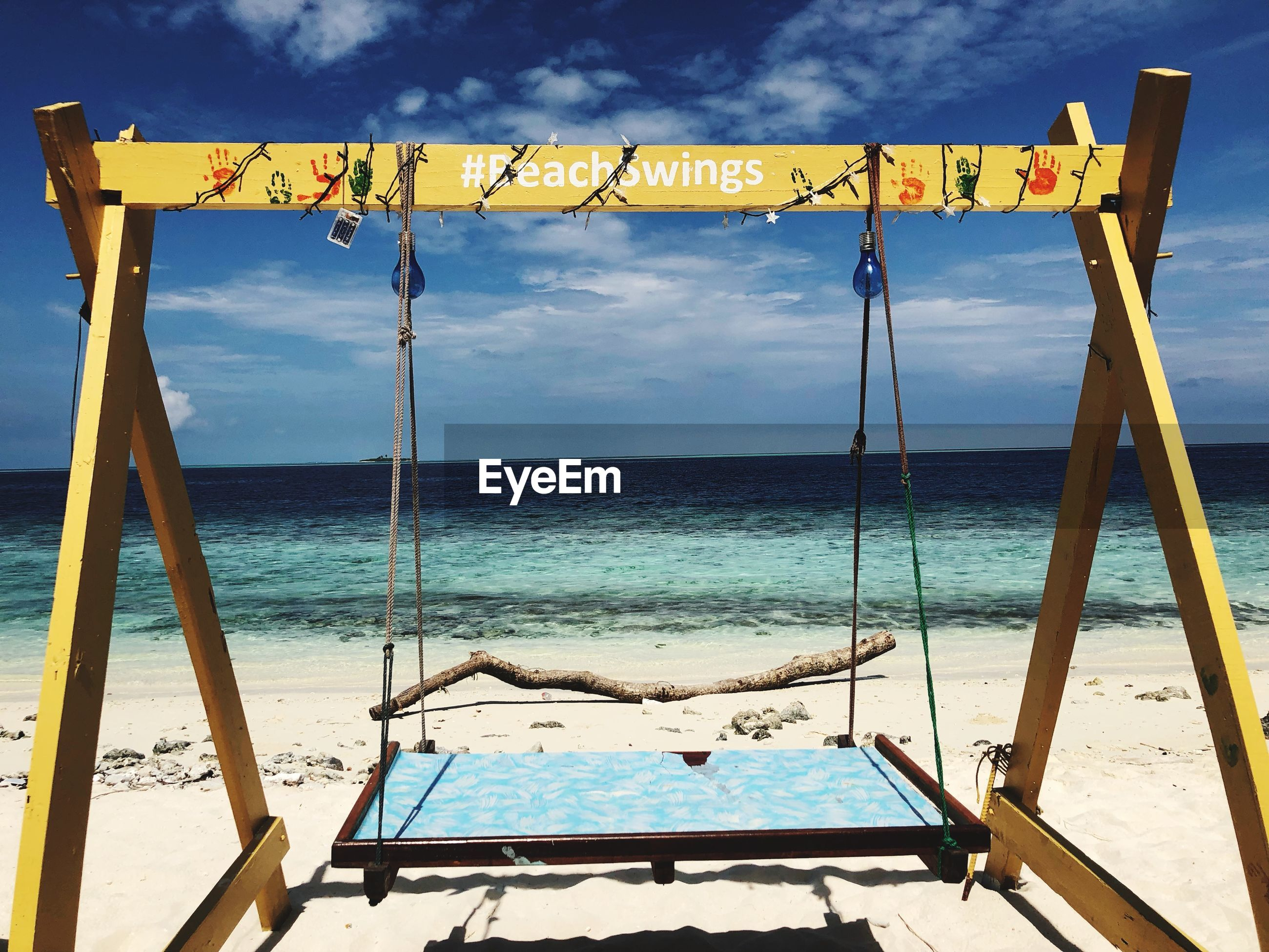 Scenic view of swing at beach against cloudy sky