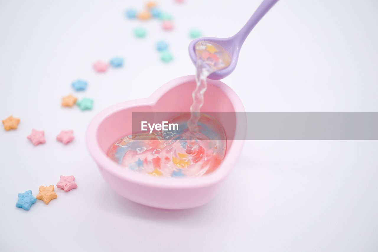 indoors, multi colored, food, sweet food, still life, studio shot, white background, food and drink, close-up, no people, kitchen utensil, sweet, spoon, eating utensil, candy, high angle view, indulgence, pink color, focus on foreground, temptation