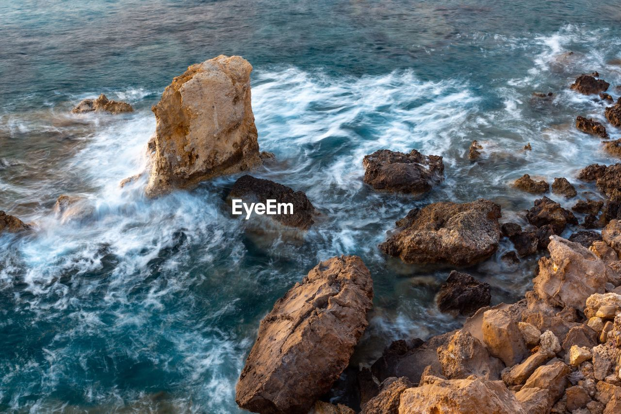 rock, sea, solid, rock - object, water, motion, wave, sport, beauty in nature, land, beach, surfing, nature, rock formation, aquatic sport, day, high angle view, outdoors, power in nature, breaking, hitting, rocky coastline, eroded
