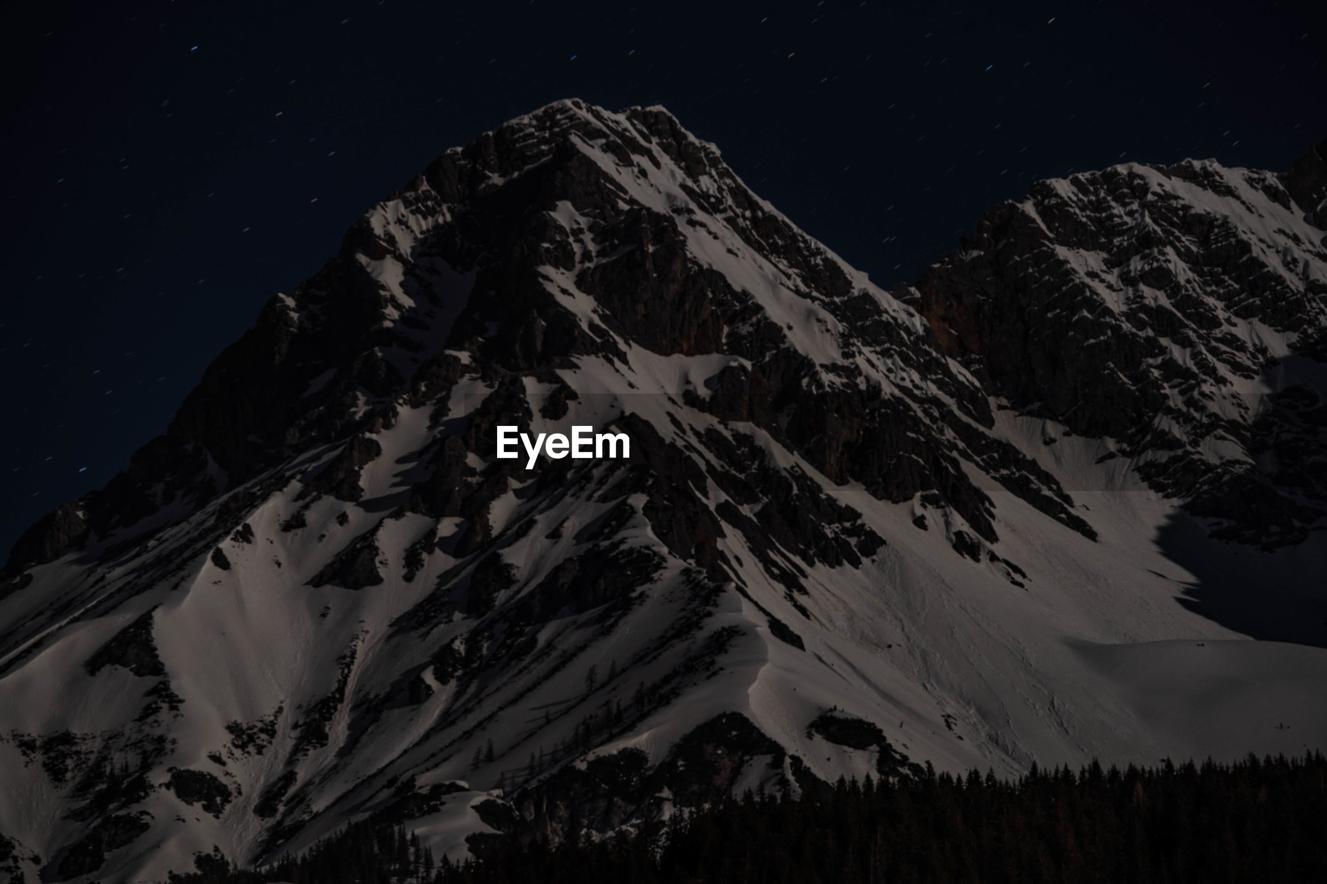 AERIAL VIEW OF SNOWCAPPED MOUNTAIN AGAINST SKY AT NIGHT
