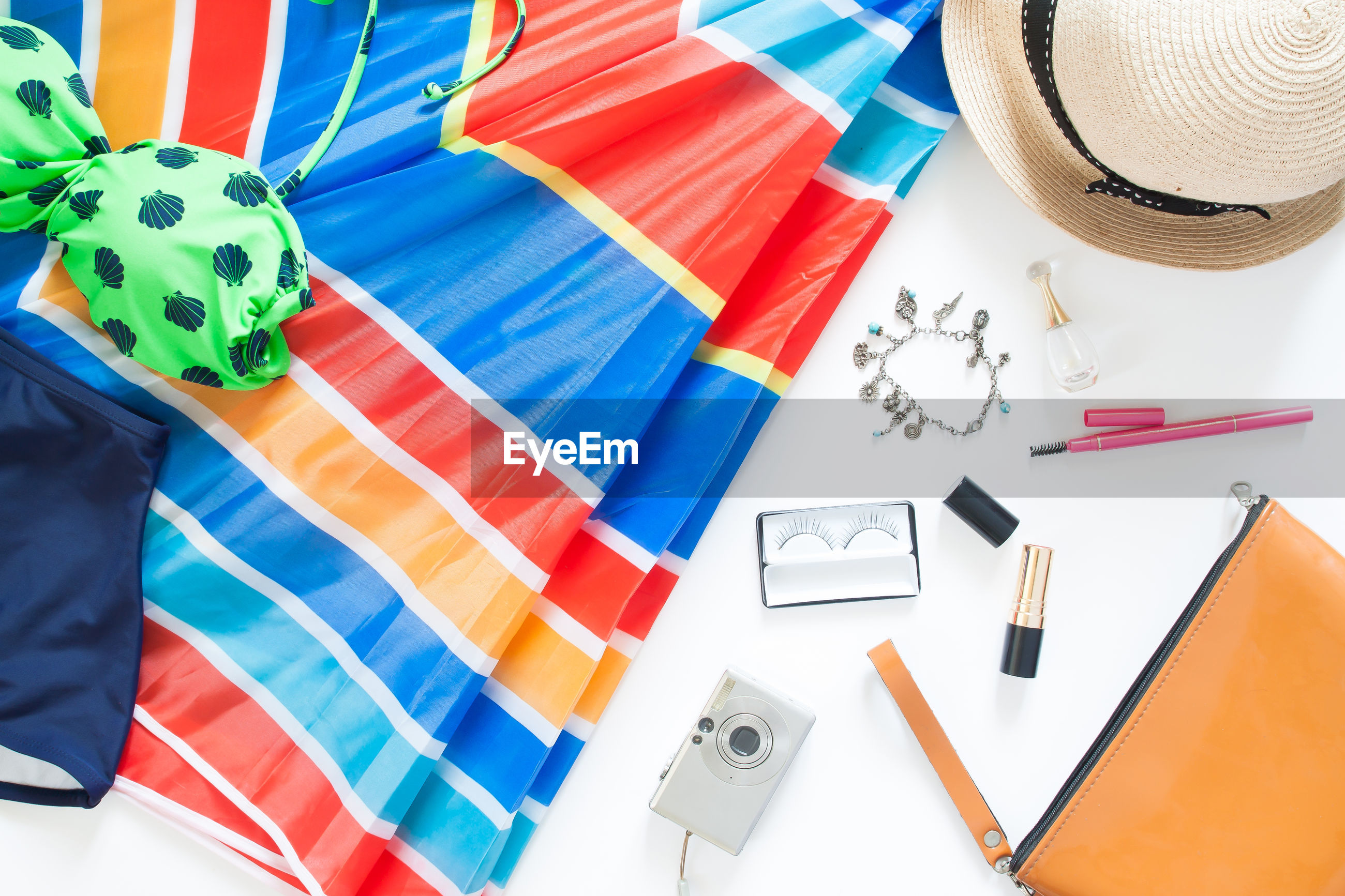 High angle view of beauty products with umbrella on table