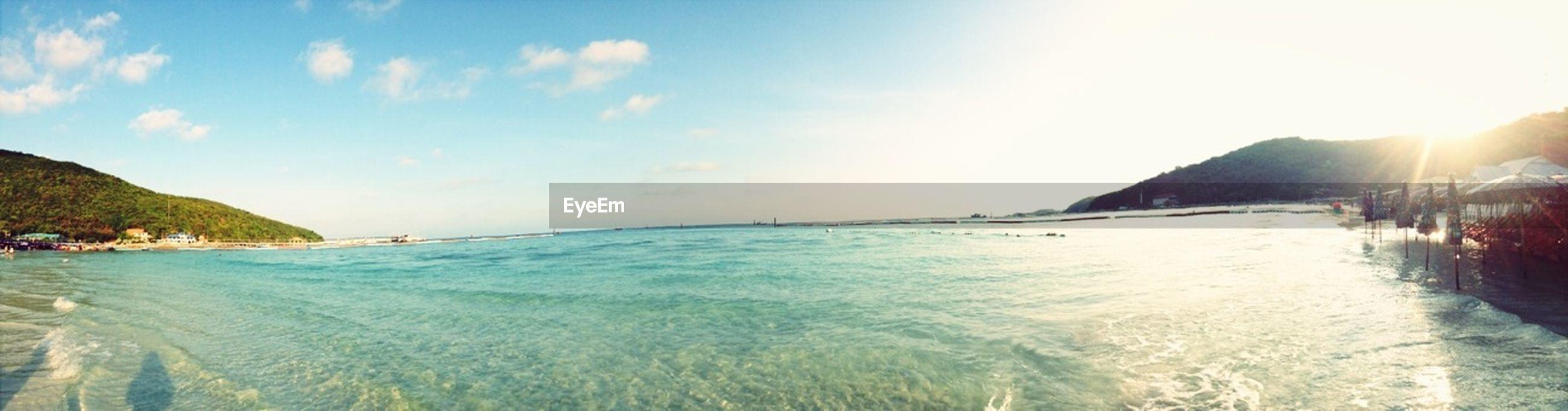 water, sea, sky, scenics, tranquil scene, beauty in nature, tranquility, beach, sun, sunlight, sunbeam, nature, mountain, lens flare, idyllic, horizon over water, panoramic, shore, nautical vessel, sunny