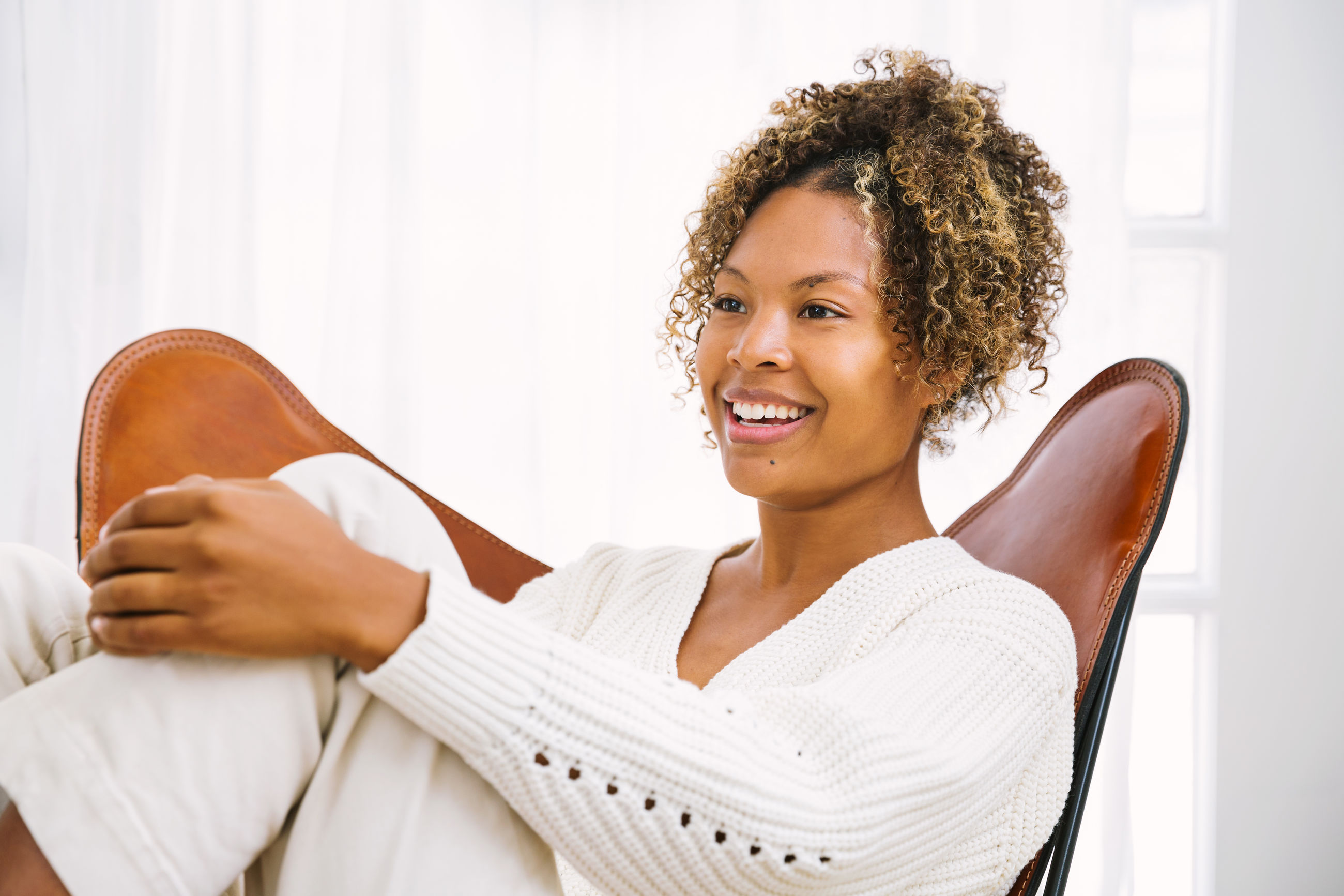 Smiling young woman sitting on chair at home