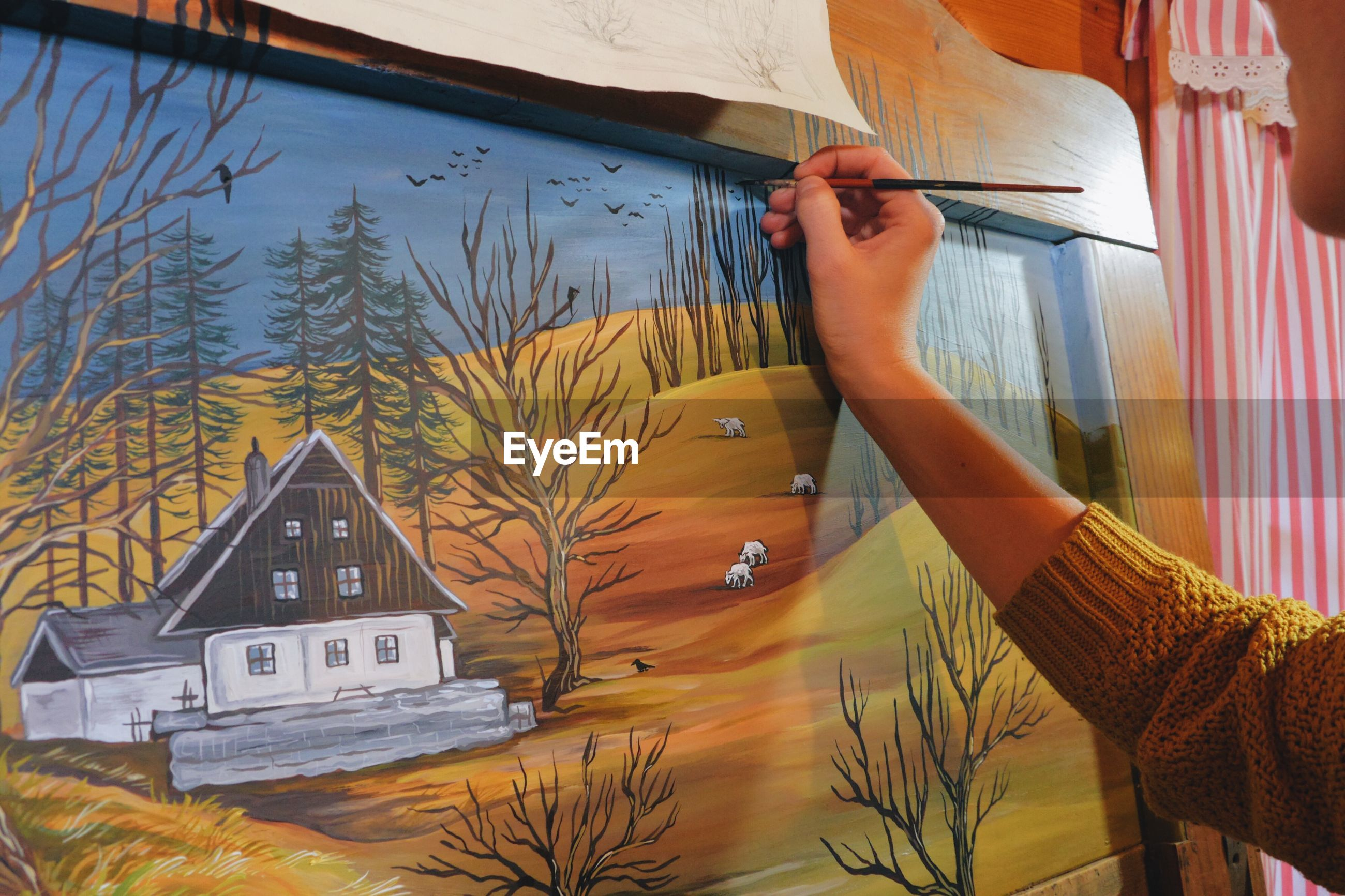 Cropped hand of woman drawing on canvas in cottage