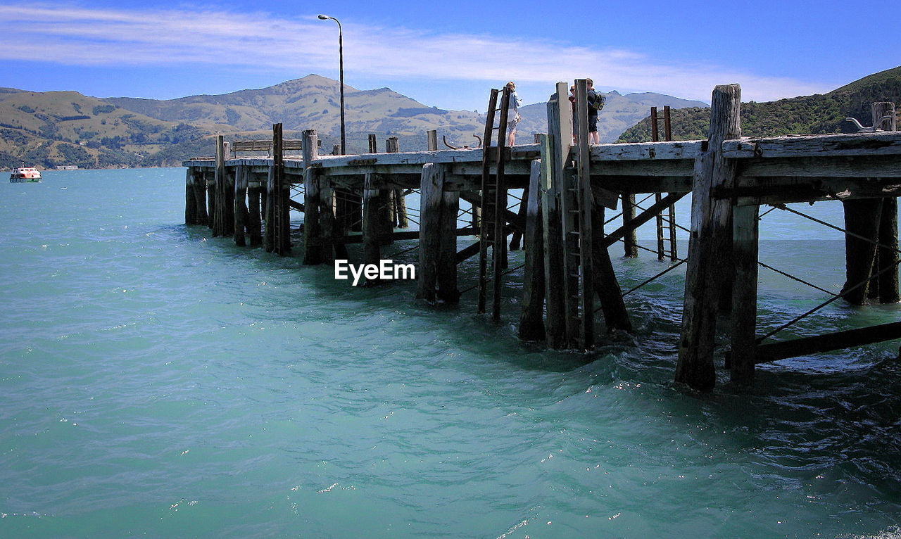 water, sky, no people, wood - material, nature, beauty in nature, tranquil scene, scenics - nature, mountain, pier, day, built structure, architecture, tranquility, sea, railing, outdoors, waterfront, idyllic, wooden post, post