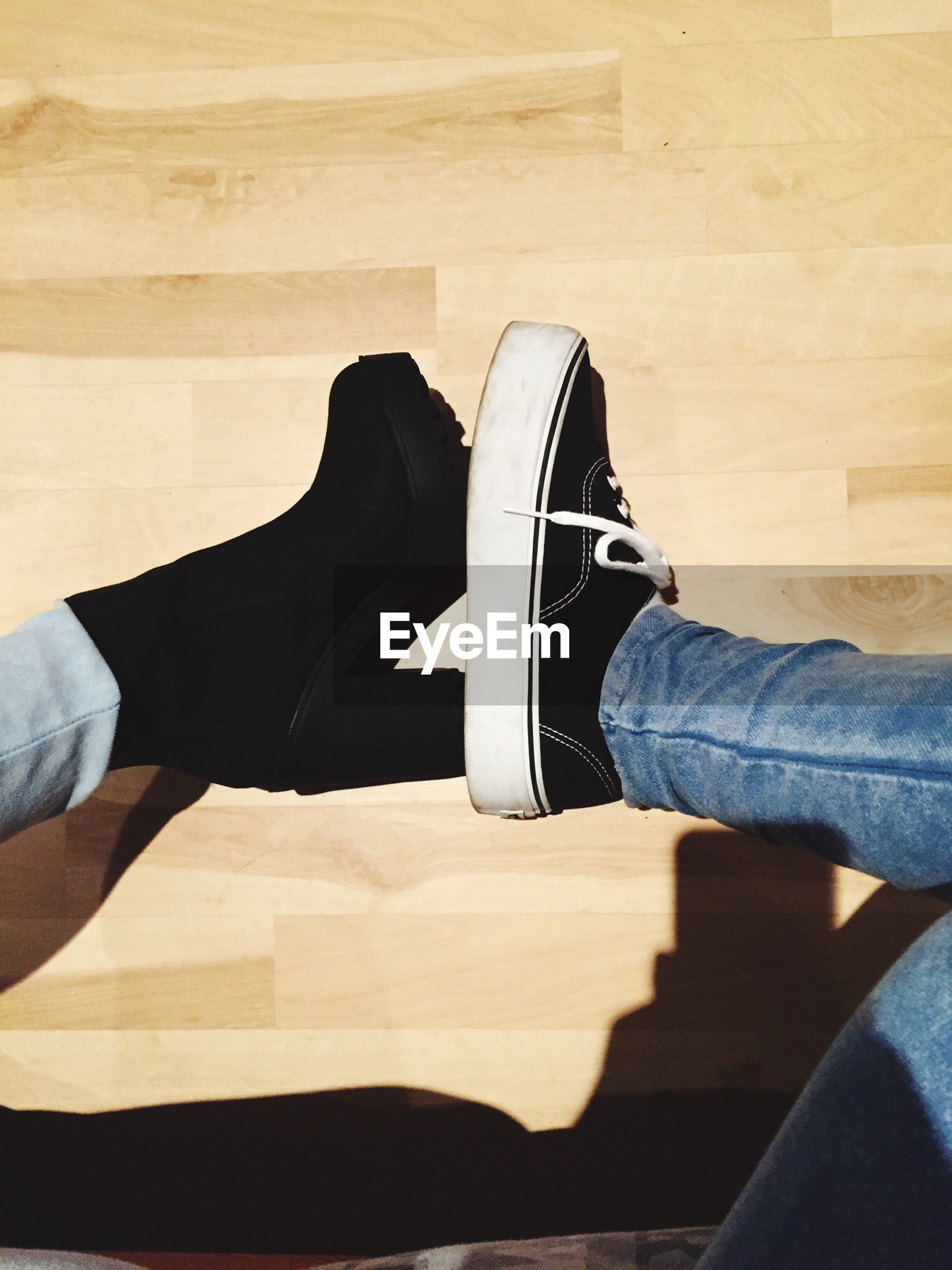 low section, lifestyles, person, shoe, leisure activity, men, jeans, sitting, standing, personal perspective, footwear, casual clothing, high angle view, indoors, human foot, relaxation, sunlight