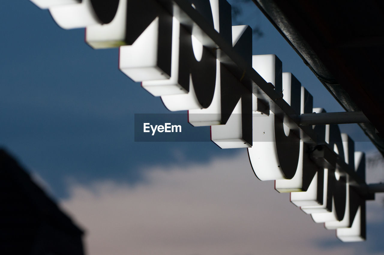 Low angle view of store sign against sky
