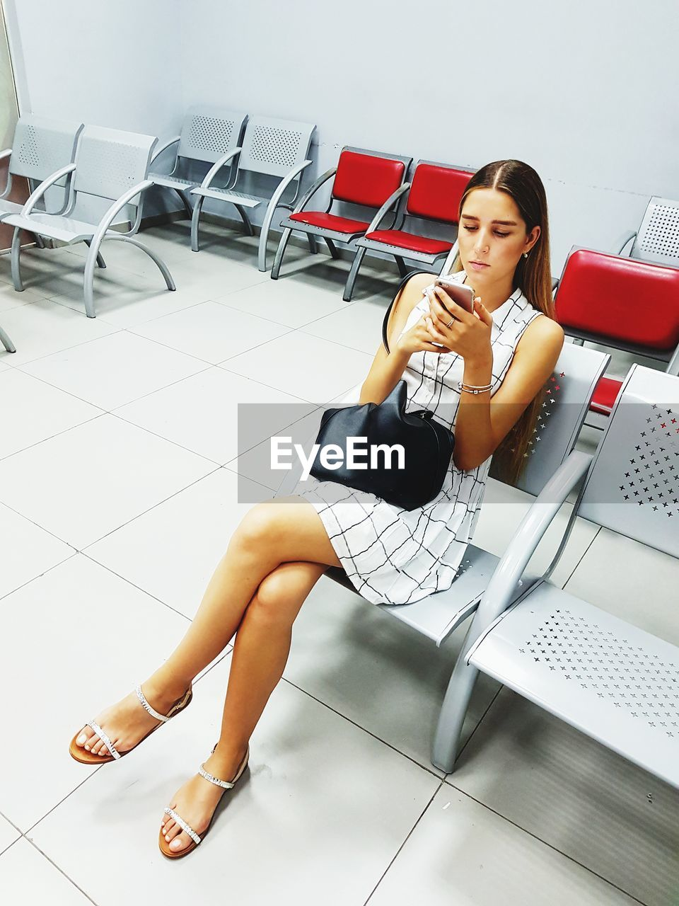 Young woman using smart phone while waiting in office