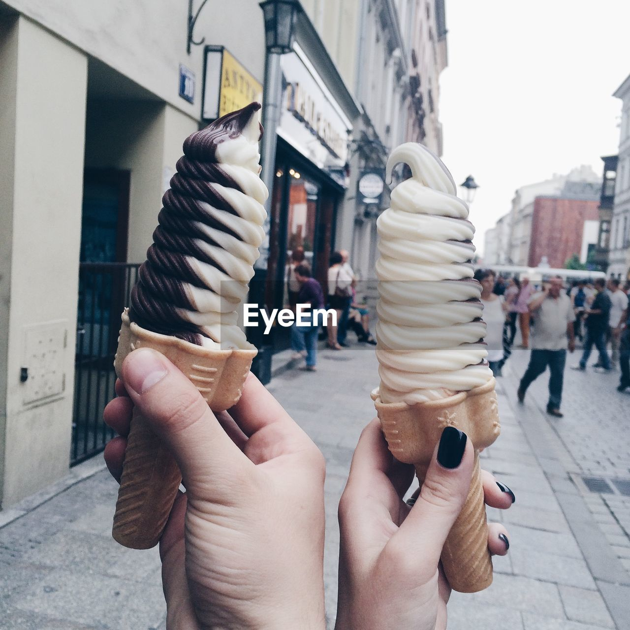 Cropped Hands Holding Swirled Ice Cream Cone Against Buildings