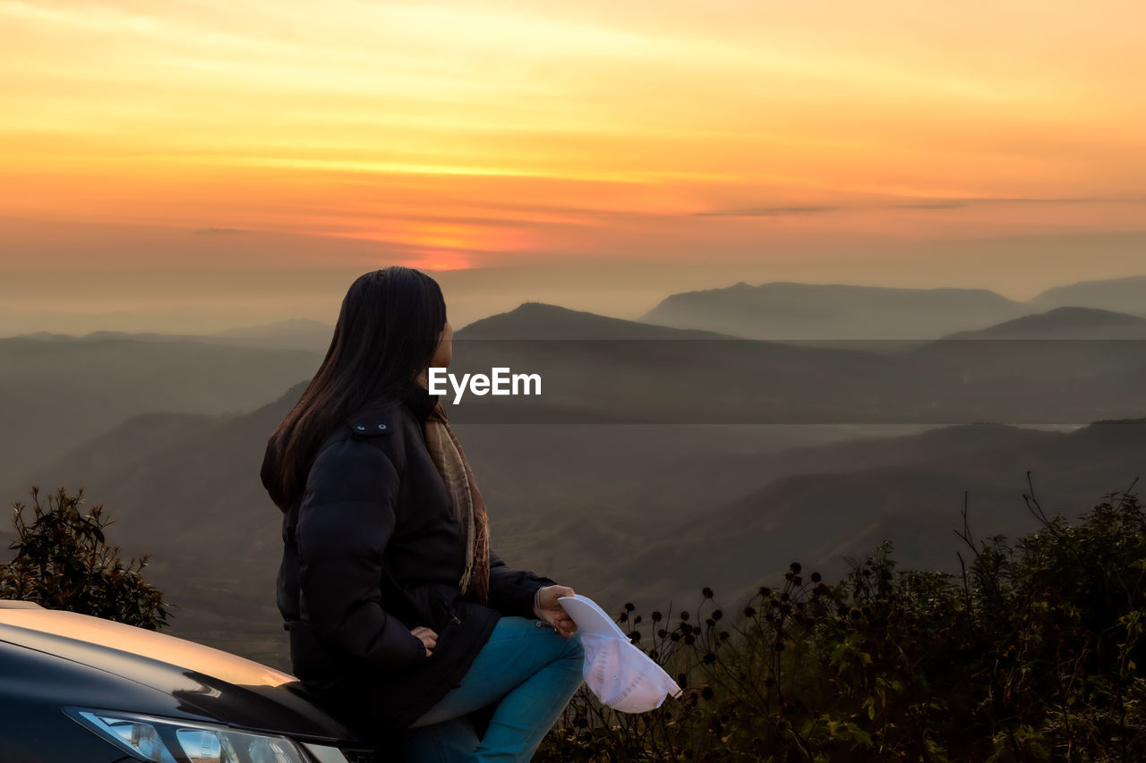 WOMAN LOOKING AT MOUNTAINS DURING SUNSET