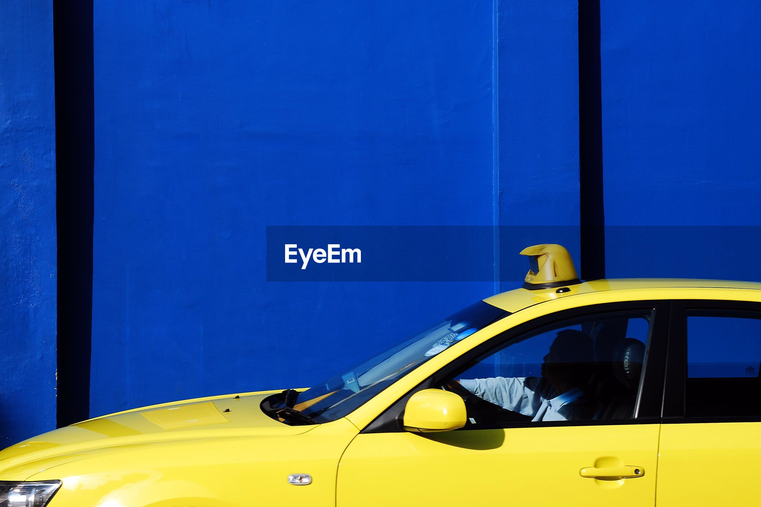 Yellow taxi by blue wall