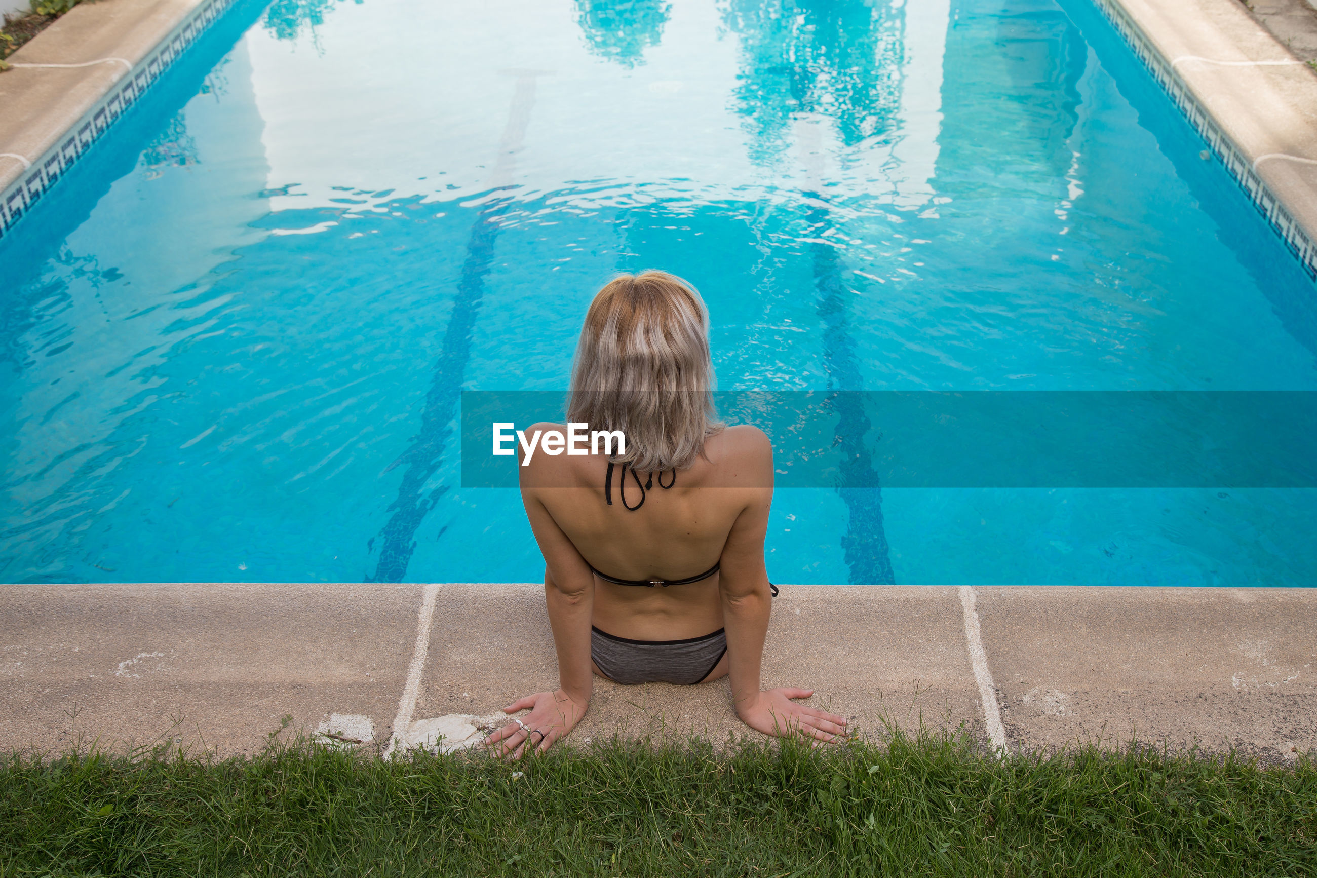 High angle view of woman sitting by swimming pool
