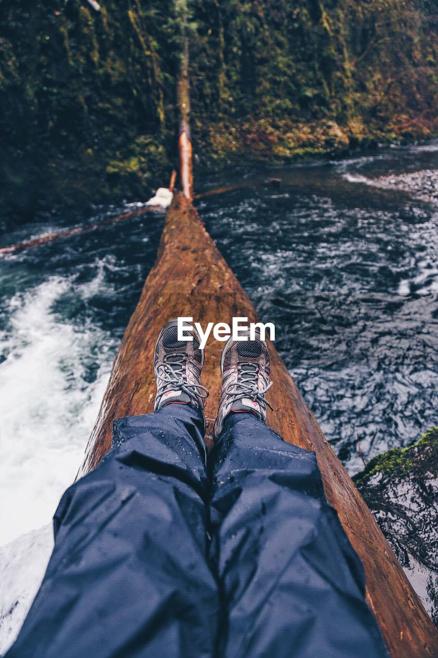 Low section of man sitting on log over river in forest