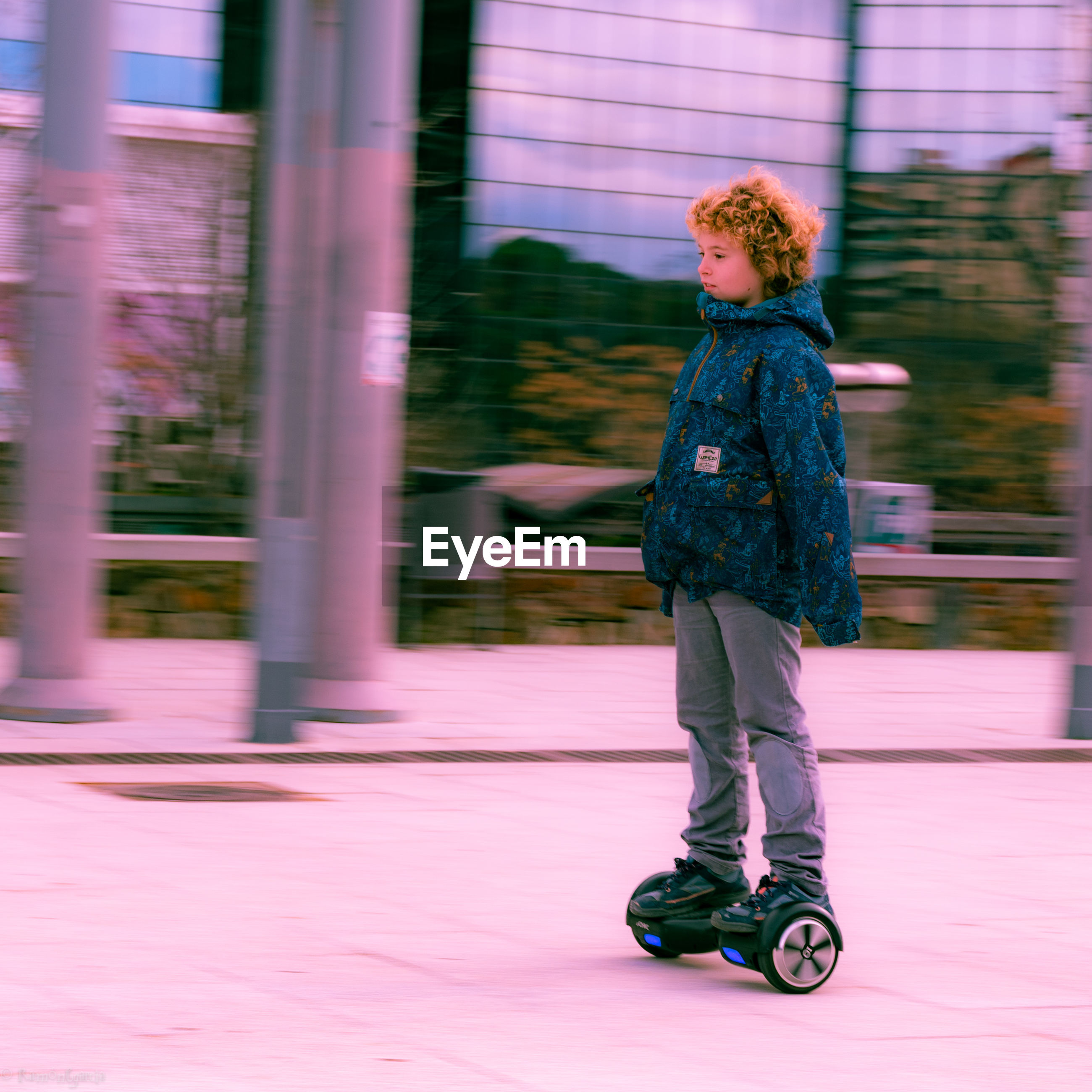 Full length of boy riding hoverboard on footpath in city