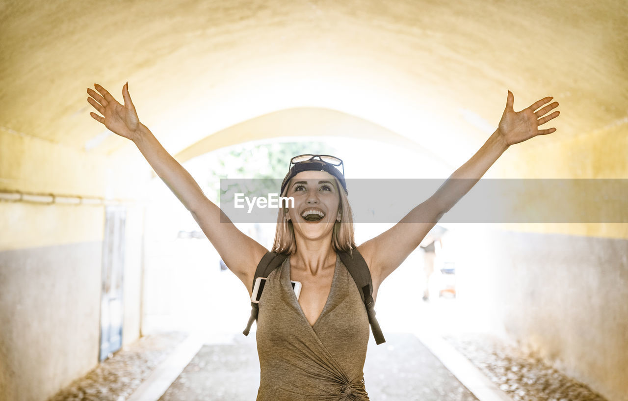 Smiling young woman with arms raised standing in tunnel