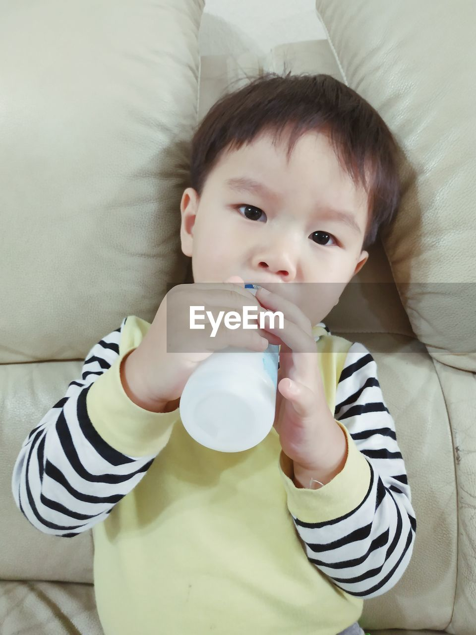Portrait of cute baby boy drinking milk on sofa at home