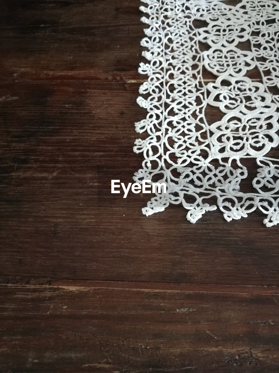 indoors, wood - material, table, pattern, no people, still life, directly above, brown, close-up, creativity, high angle view, wood, decoration, art and craft, white color, flooring, design, craft, celebration, floral pattern, embroidery