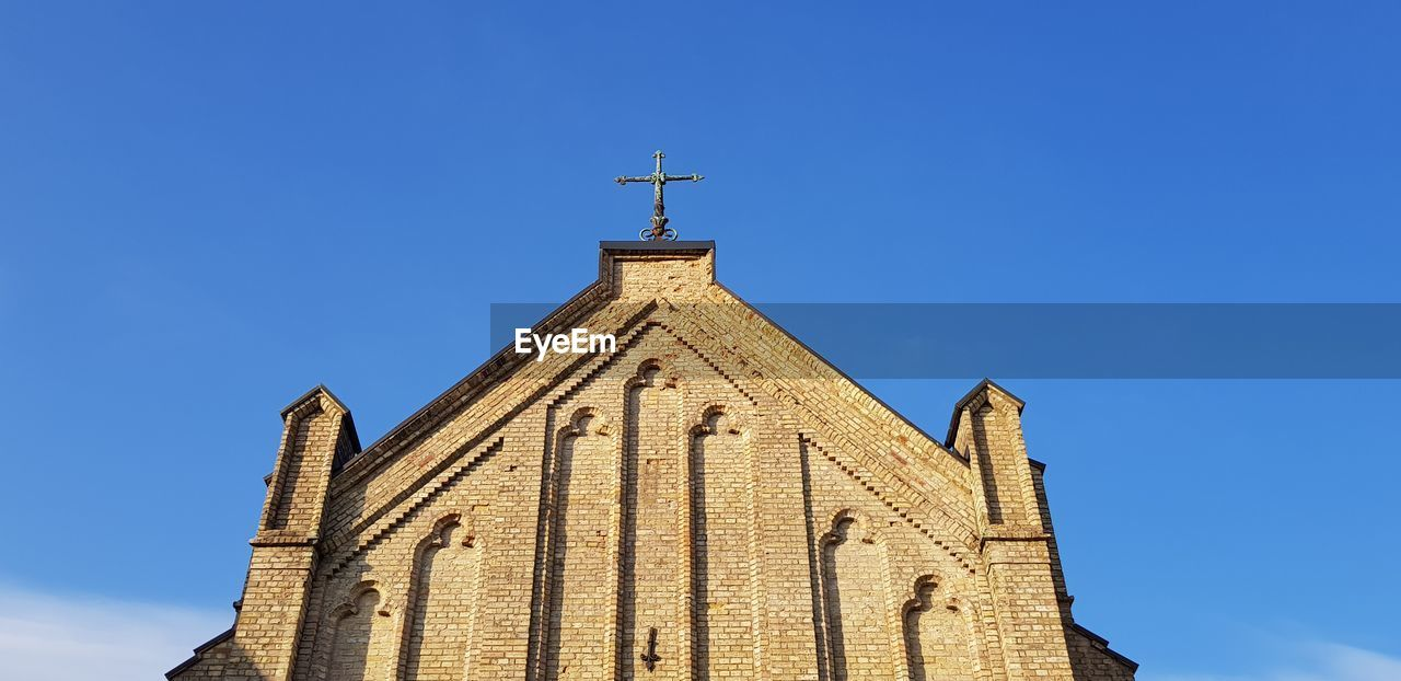 religion, belief, spirituality, built structure, sky, architecture, place of worship, low angle view, building, building exterior, blue, cross, nature, clear sky, no people, day, sunlight, outdoors, spire