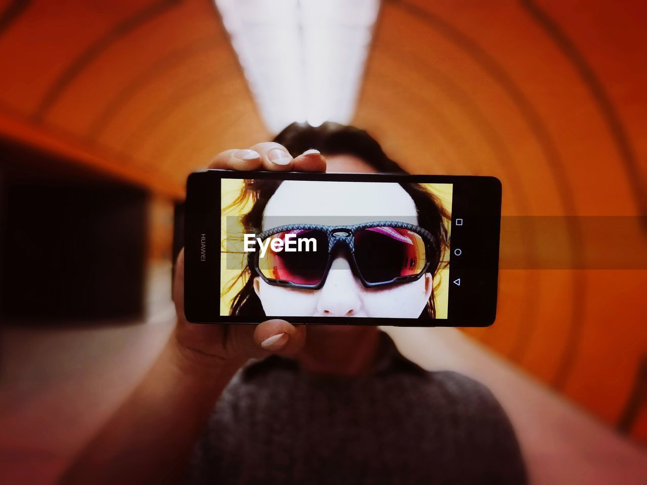 Close-up of woman taking selfie from mobile phone in tunnel