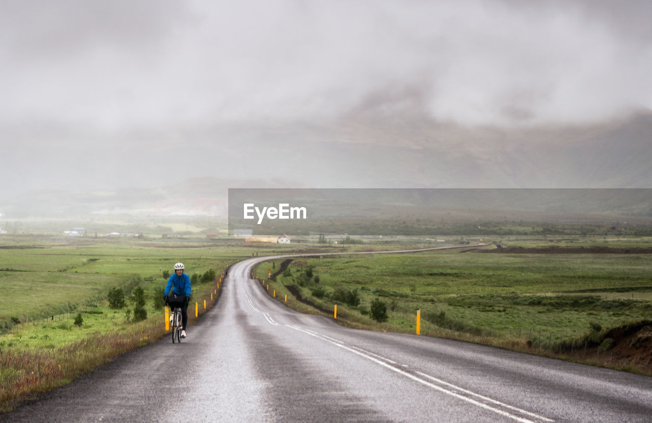 Rear View Of Person Biking On Country Road Along Landscape