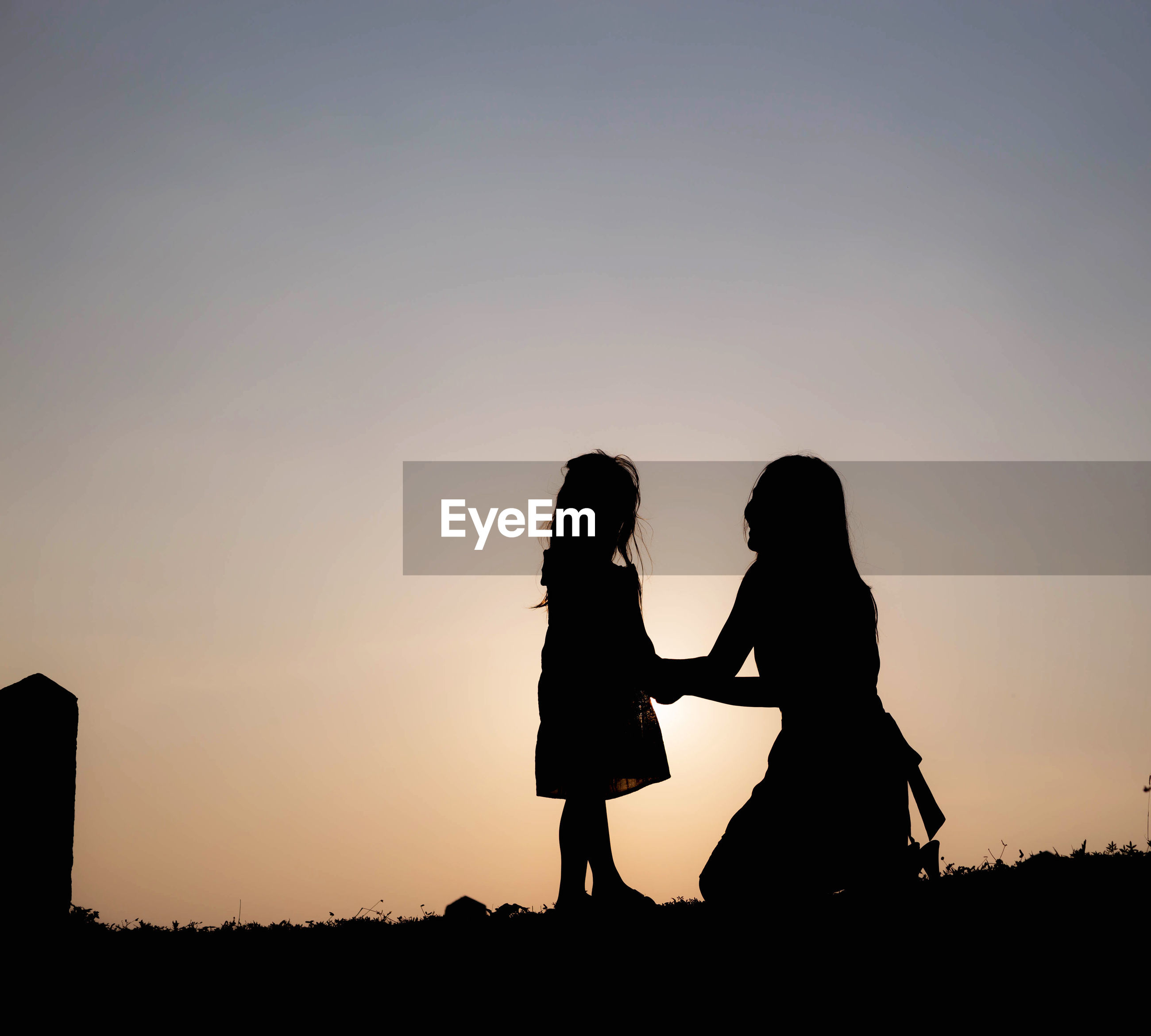 Silhouette woman with daughter on field against clear sky during sunset