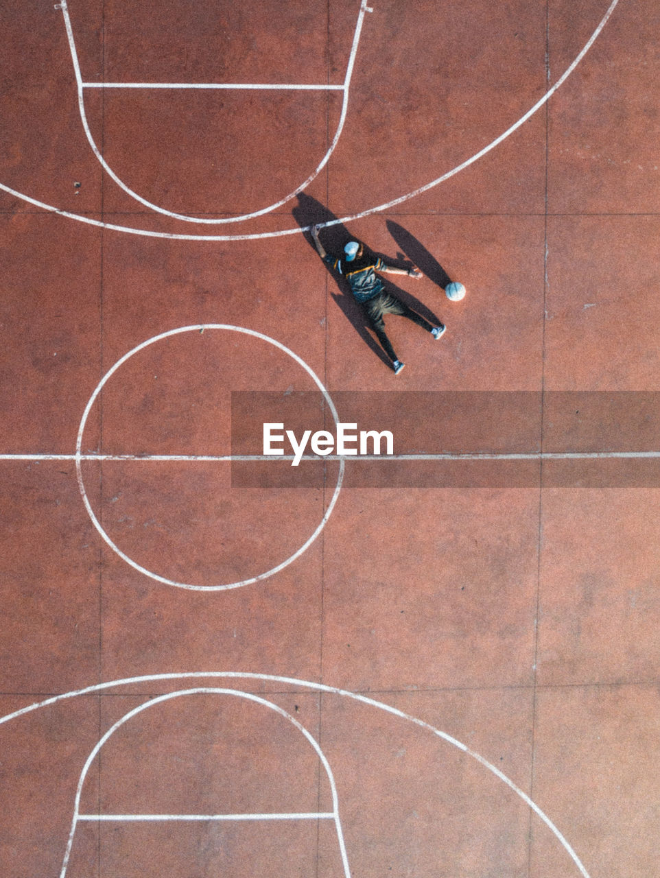 Aerial view of man lying on floor at basketball court