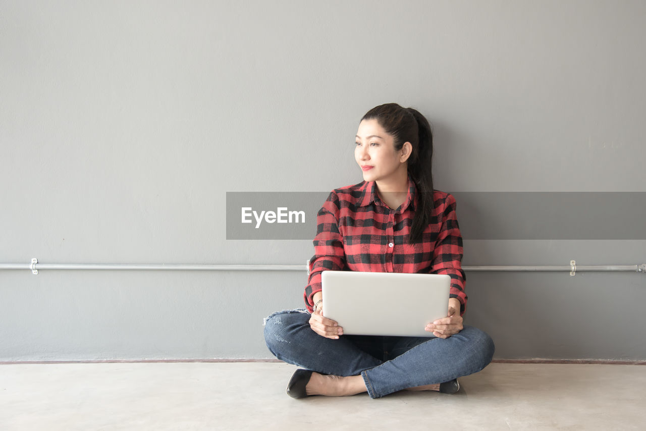 Woman siting with laptop against wall