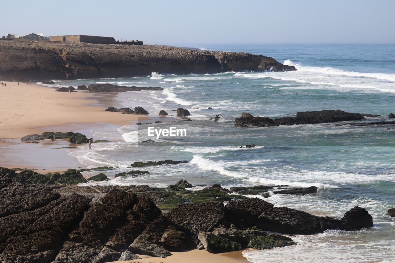 Distant view of fort on rock formation at beach against sky