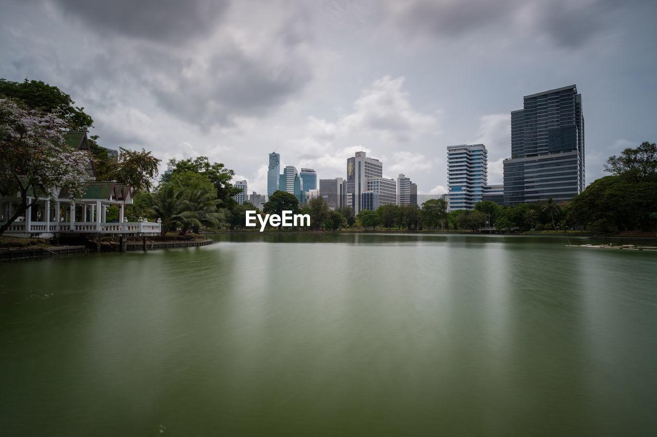 Lake By Buildings Against Sky In City