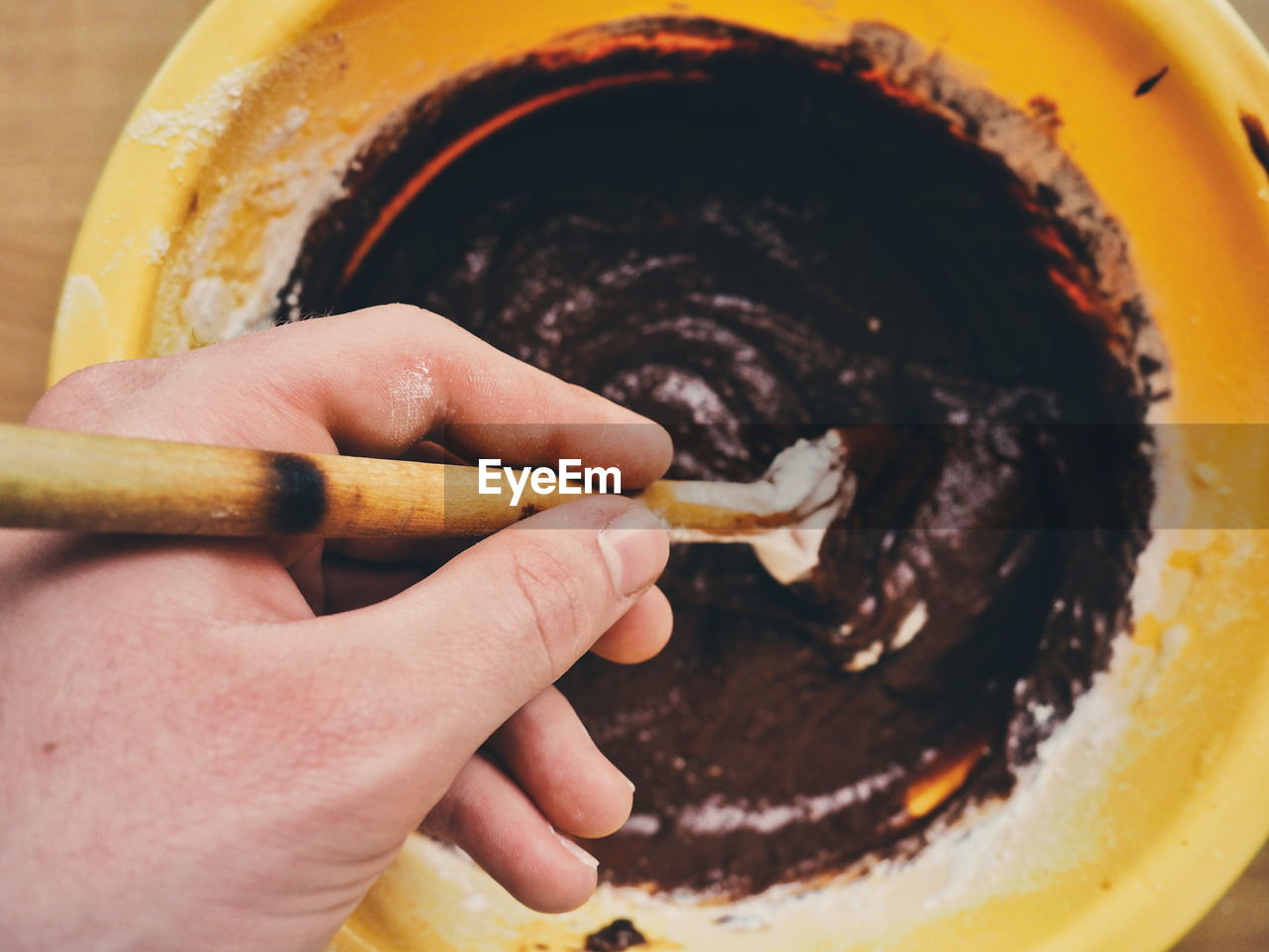Cropped Image Of Hand Steering Chocolate Cake Batter In Container