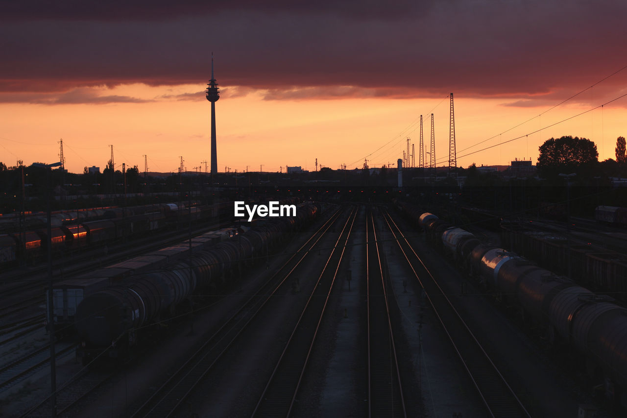 sky, sunset, rail transportation, railroad track, track, transportation, architecture, built structure, nature, cloud - sky, public transportation, no people, mode of transportation, building exterior, train, train - vehicle, high angle view, orange color, outdoors, travel, shunting yard, spire, power supply