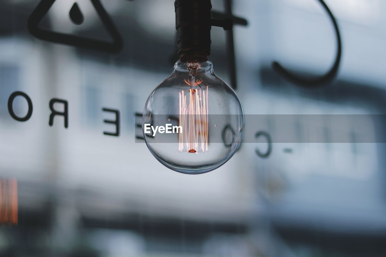 close-up, focus on foreground, no people, hanging, indoors, mode of transportation, number, vehicle interior, electricity, time, selective focus, glass - material, transportation, lighting equipment, metal, clock, transparent, control, communication, day