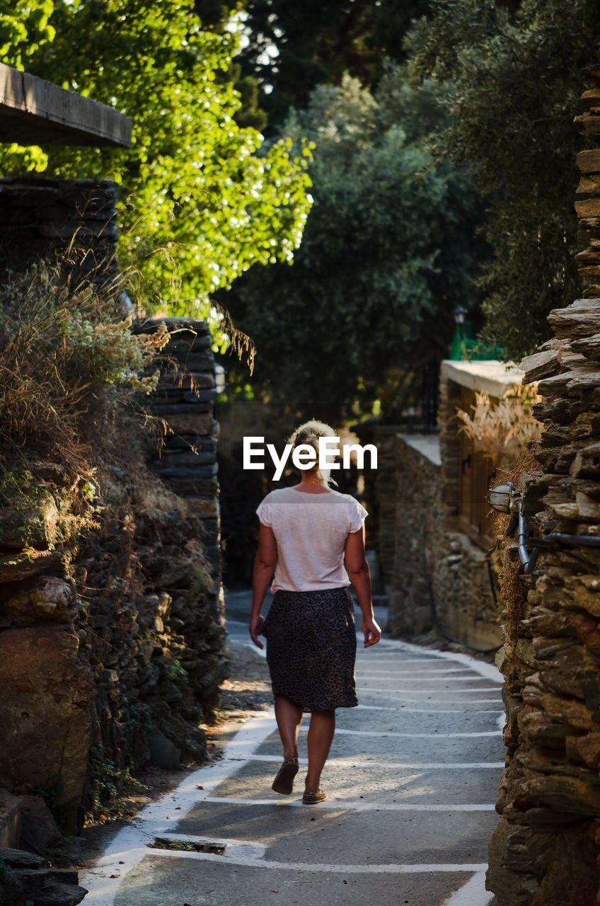 Rear View Of Woman Walking In Alley