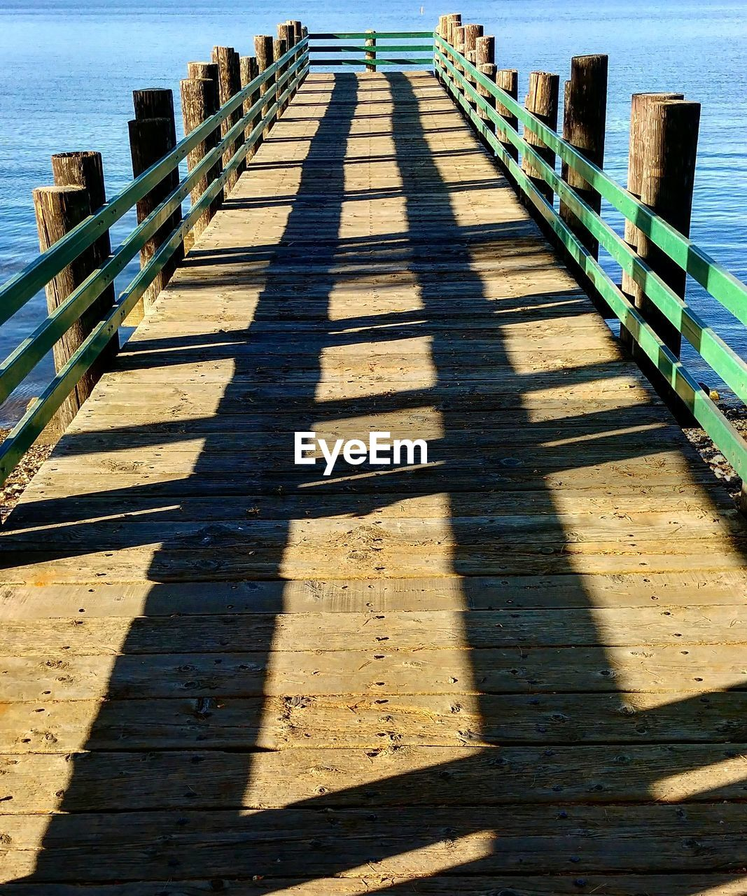 shadow, sunlight, nature, the way forward, railing, direction, day, no people, architecture, outdoors, focus on shadow, built structure, footpath, diminishing perspective, wood - material, water, pier, high angle view, sunny, wood, long