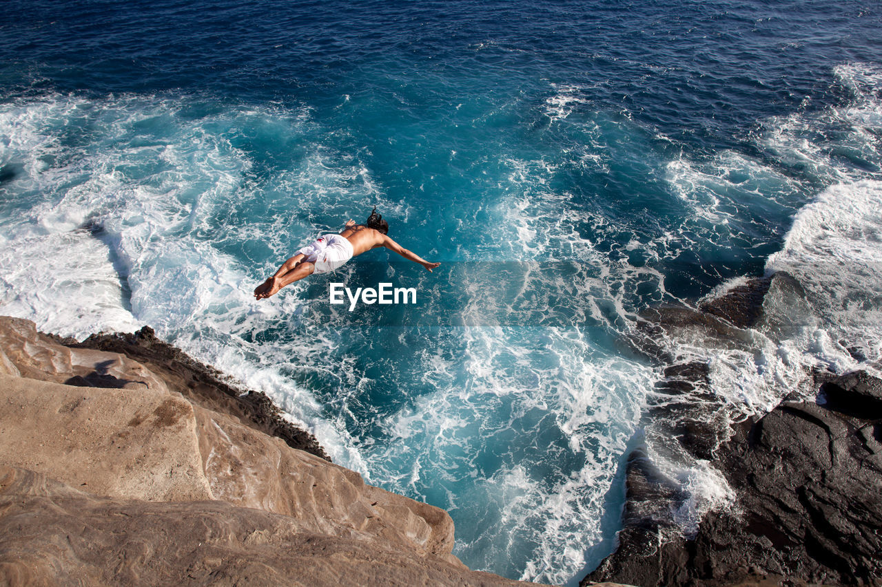 HIGH ANGLE VIEW OF PERSON SWIMMING ON ROCKS