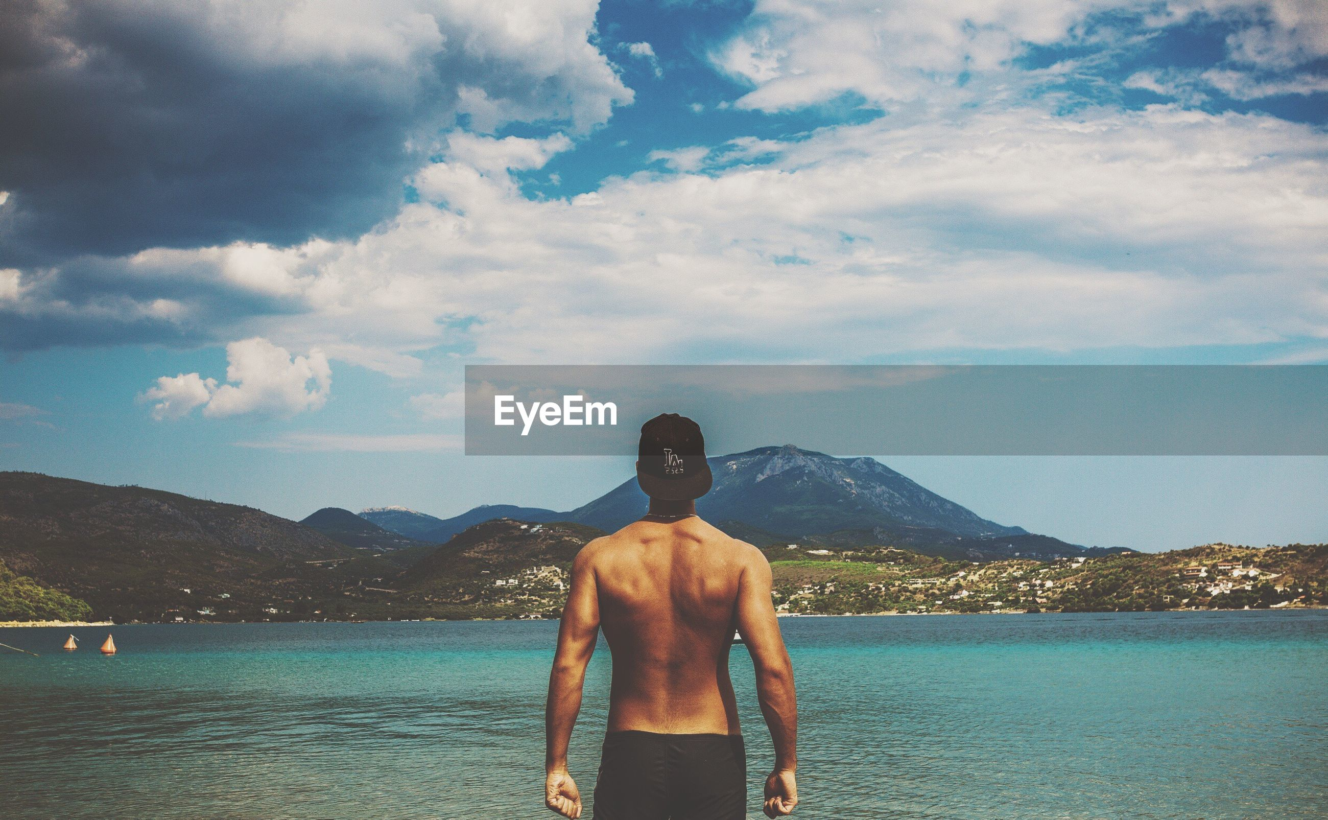 Rear view of shirtless muscular man standing by sea against sky