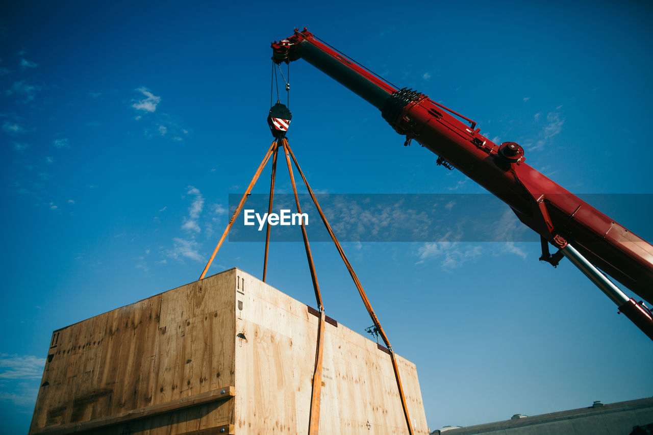 Low Angle View Of Crane Carrying Box Against Blue Sky