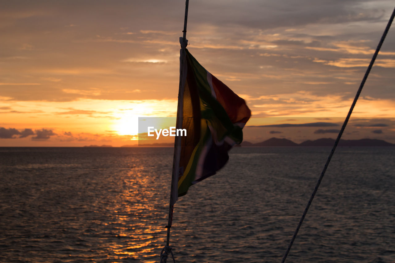 sky, sunset, flag, water, cloud - sky, patriotism, nature, beauty in nature, orange color, no people, sea, scenics - nature, pole, tranquility, outdoors, tranquil scene, environment, waterfront