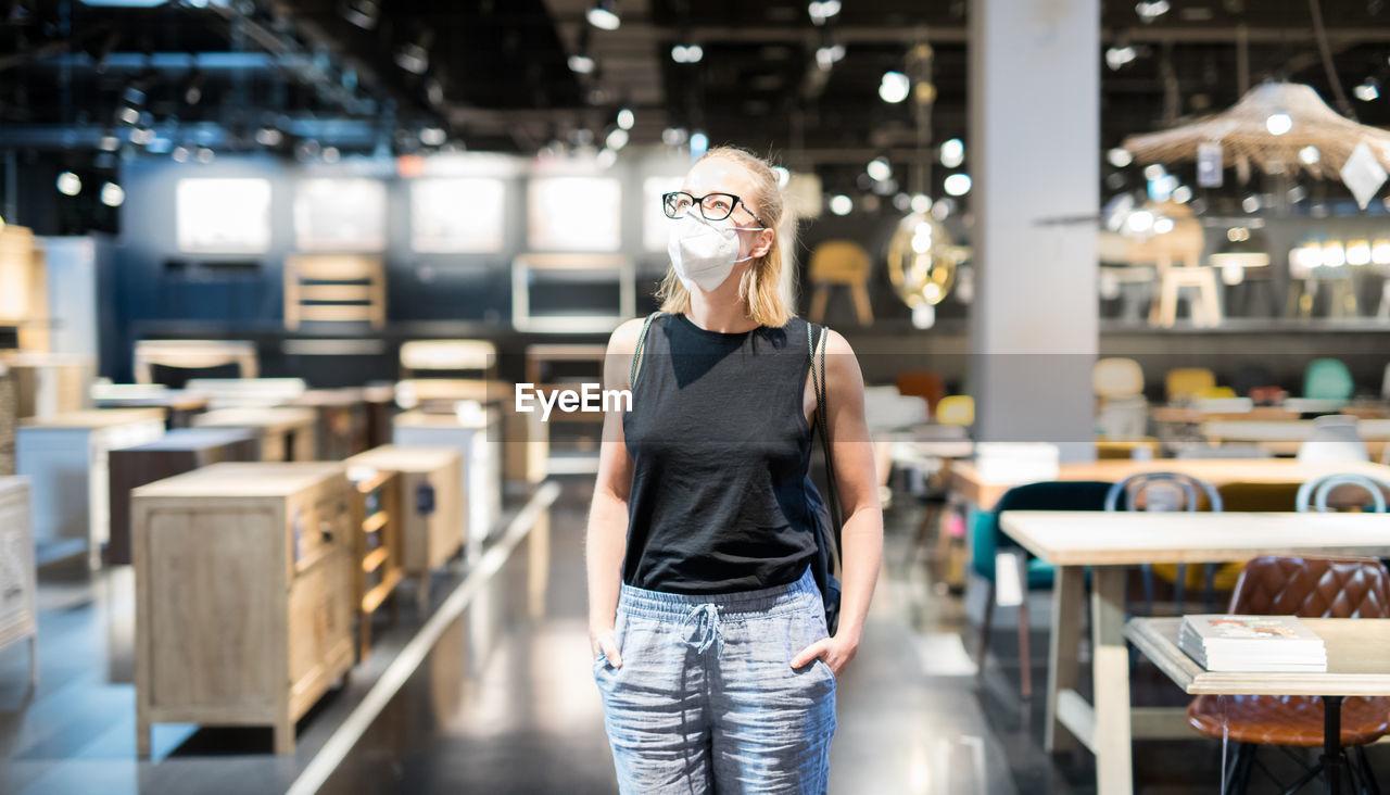 Woman wearing flu mask standing at store