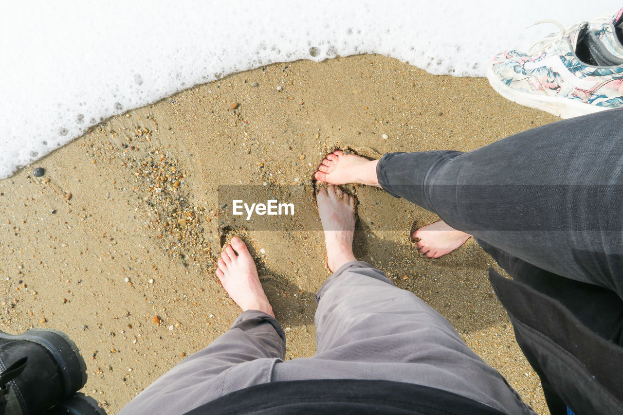 low section, human leg, real people, men, human body part, body part, personal perspective, leisure activity, high angle view, lifestyles, casual clothing, standing, people, two people, directly above, shoe, day, adult, land, nature, jeans, outdoors, human foot, couple - relationship, human limb