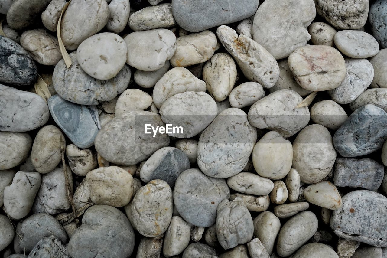 solid, large group of objects, stone - object, rock, pebble, stone, backgrounds, no people, full frame, textured, abundance, day, rock - object, nature, high angle view, outdoors, directly above, close-up, rough, still life